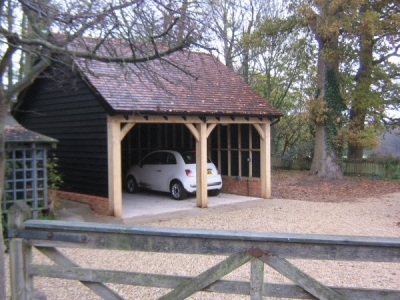 2 Bay Timber Garage in green Oak, built by Suffolk Cart lodges in Bury St Edmunds Suffolk. With green oak and cedar shingle tiles.