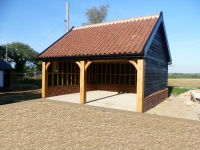 Green Oak Garage built by Suffolk Cart Lodges in Ipswich Suffolk. Open bays with timber frame on display.